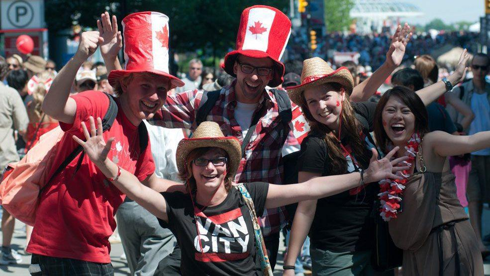 Group of people posing for a picture with Canadian flag hats, shirts, and other clothing during a parade