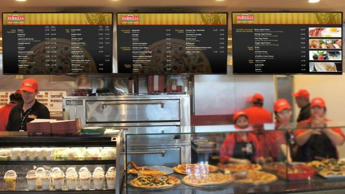 Three panel digital menu board implemented at Famous Famiglia Pizza hangs above the restaurant counter