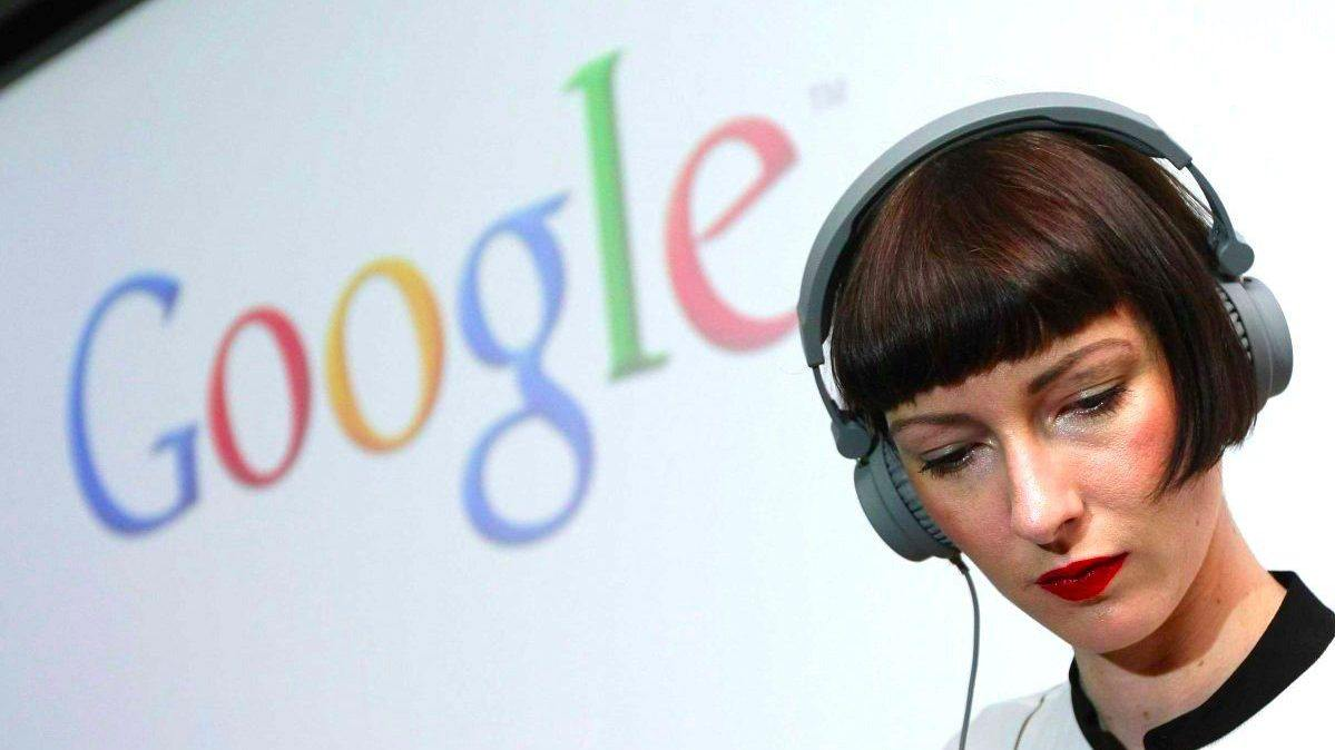 Woman wearing headphones with the Google logo behind her