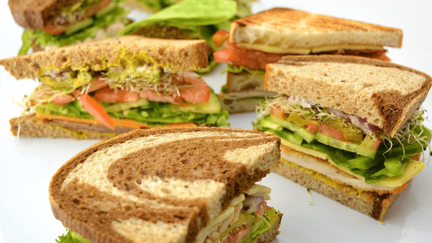 Photo of several sandwiches from the Delly at UBC cut in half facing the camera