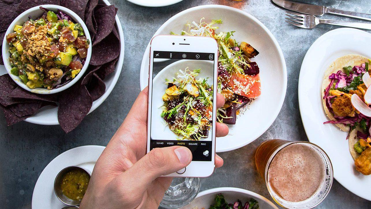 Top down view of a person taking a photo of their meal with a smartphone