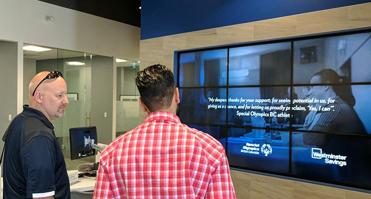 Two men looking at the newly installed video wall at a Westminster Savings Credit Union branch