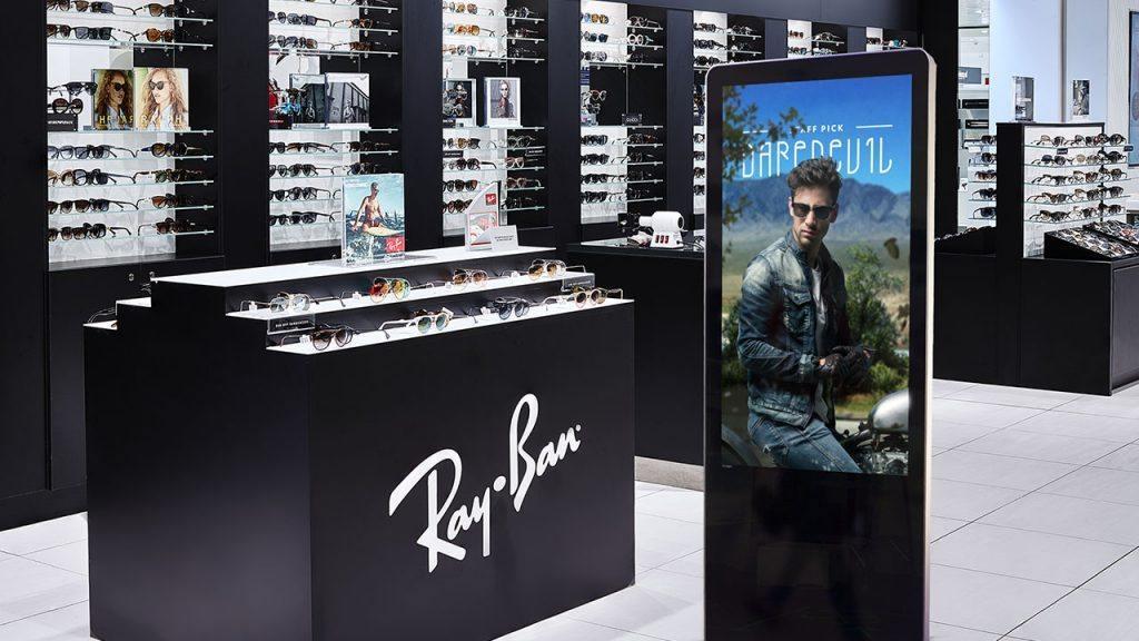 Digital signage kiosk display showing a branding design inside of a trendy eyewear store