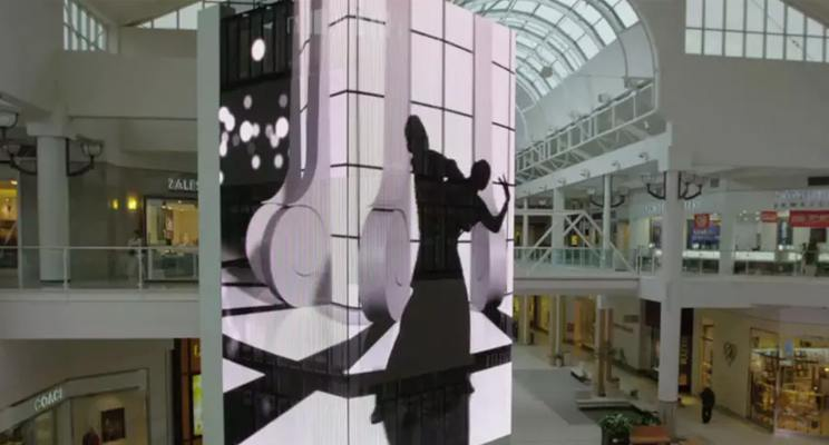 Digital signage displayed on the pillar of a mall showing artistic content