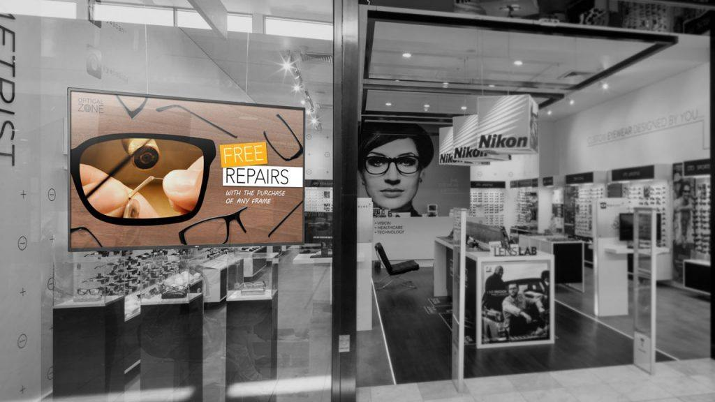 Digital signage TV display mounted inside the front window of an eyewear store showing a promotion for free repairs