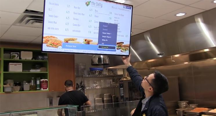 Kuusoft support engineer installs a digital menu board for the Delly, a quick service restaurant at UBC