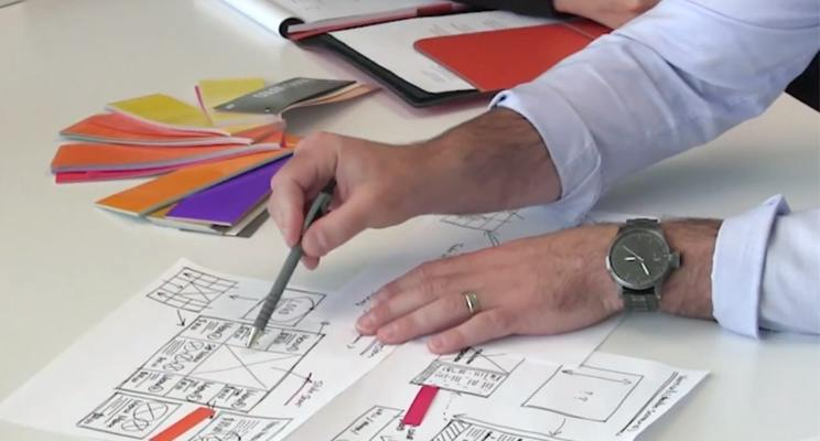 A Kuusoft digital menu board specialist performs consultation with wireframes for a client