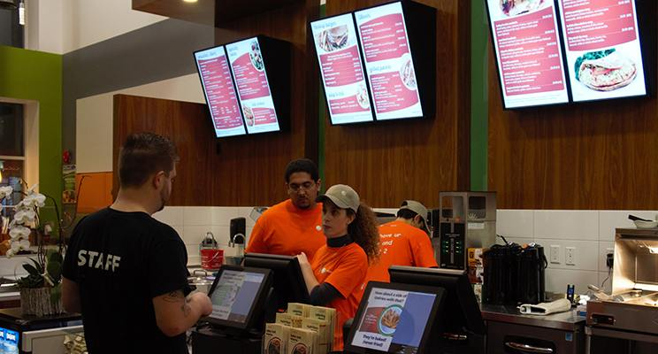 An employee takes the order of a customer at a quick service restaurant with NexSigns digital menu boards