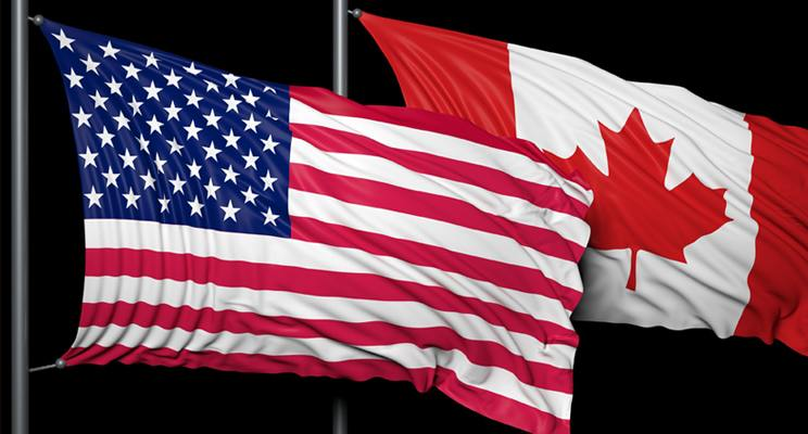 American and Canadian flags fly on flagpoles side-by-side