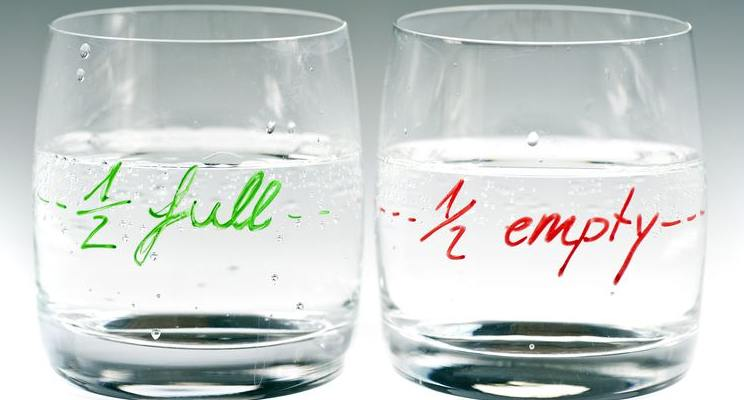 Two glasses with the same water level on marked half full and the other half empty