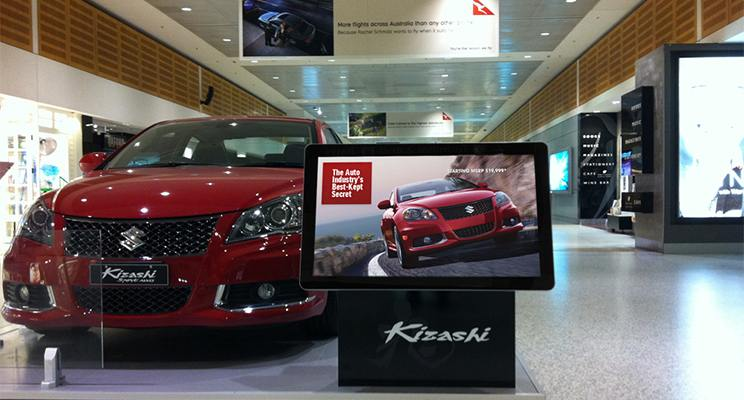 Digital signage tv promoting a car in front of the same car model on a dealership show floor