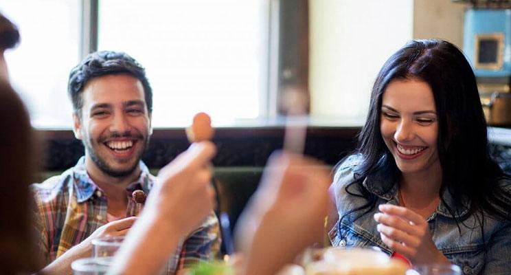 Smiling couple enjoying a meal at a restaurant with their friends
