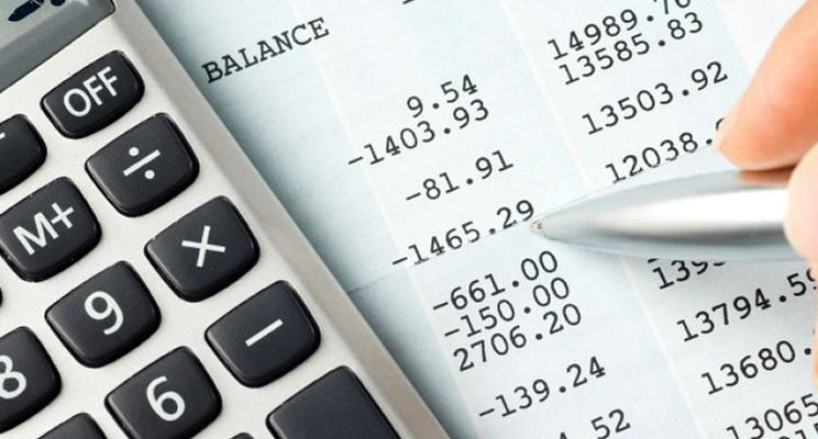 Close view of a balance sheet with a calculator and pen on top of it