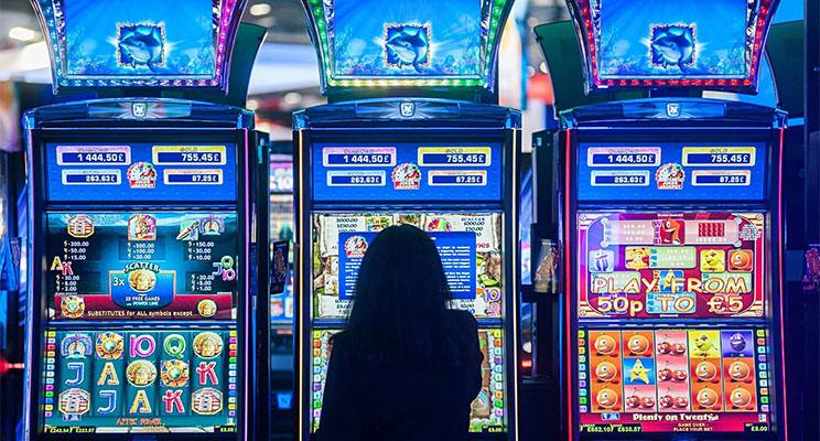 Woman sitting at a slot machine with the machine backlighting with its vibrant digital displays