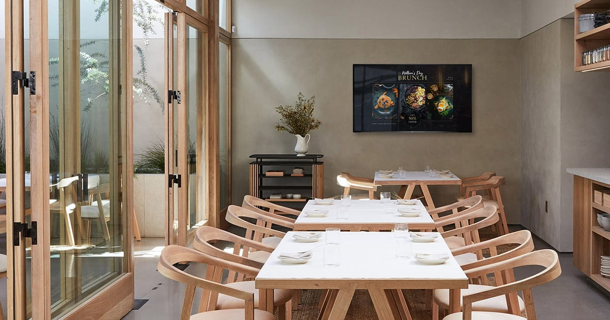 a restaurant with nice tables and window and digital signage on the wall