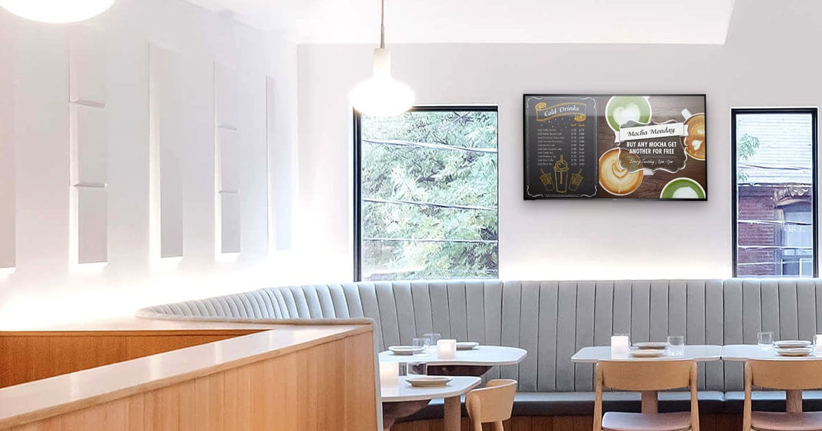 well lit restaurant interior with tables and windows and digital sigange