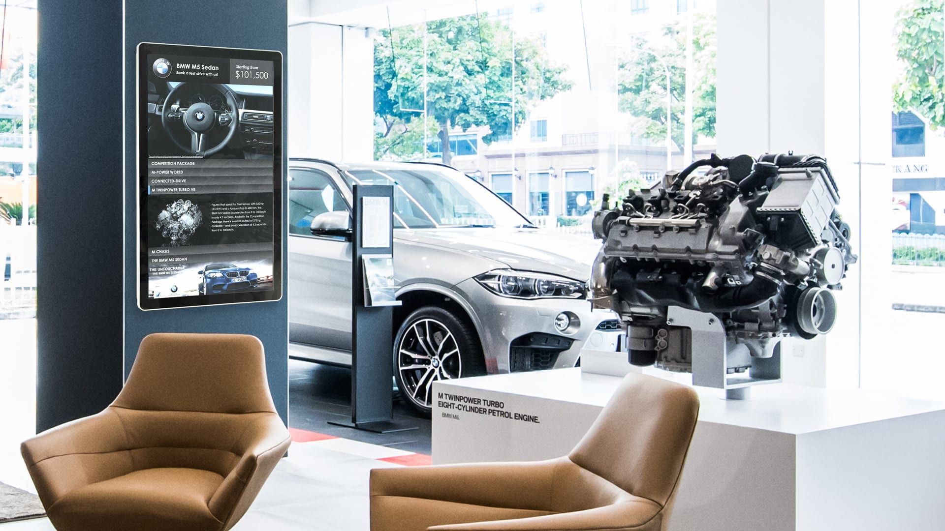 BMW auto dealer retail shop with sofa chairs and white bmw suv