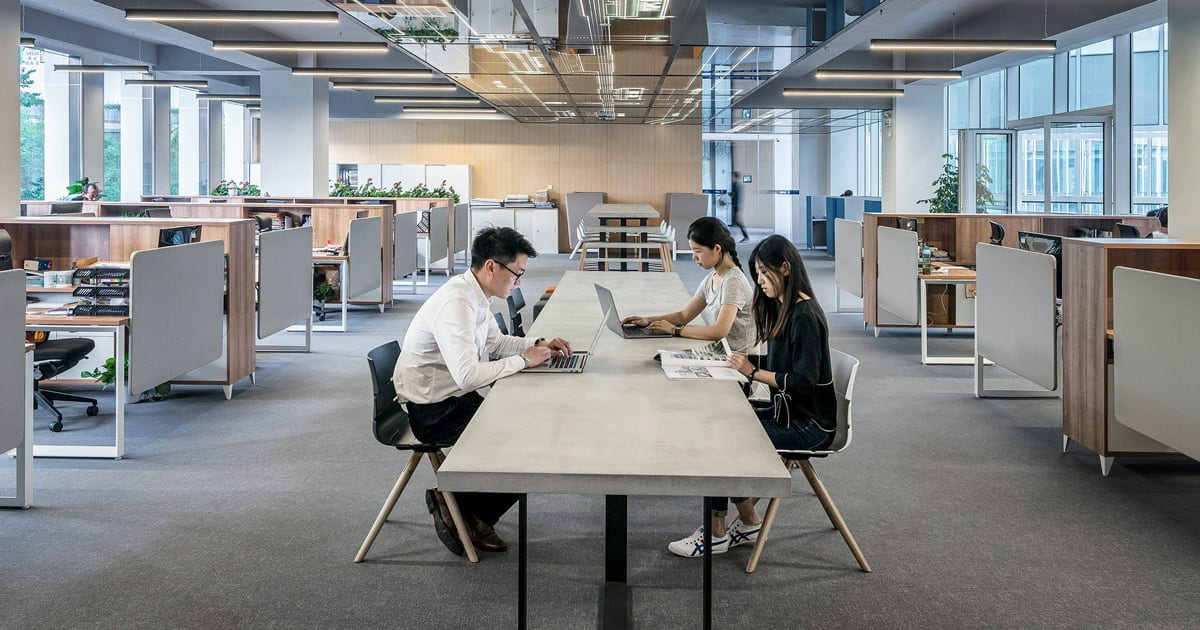 an open office workplace with communal desks and people at work