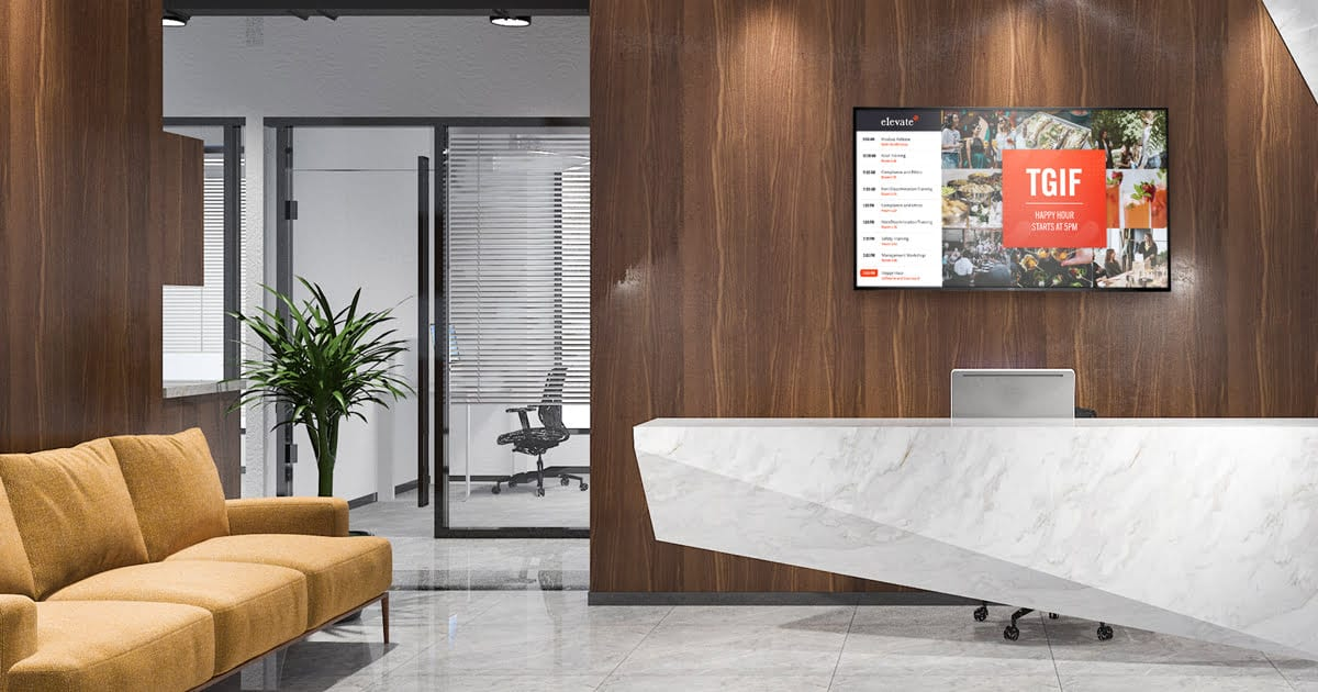 a modern lobby with sofa chairs, plant, and digital signage for office lobby