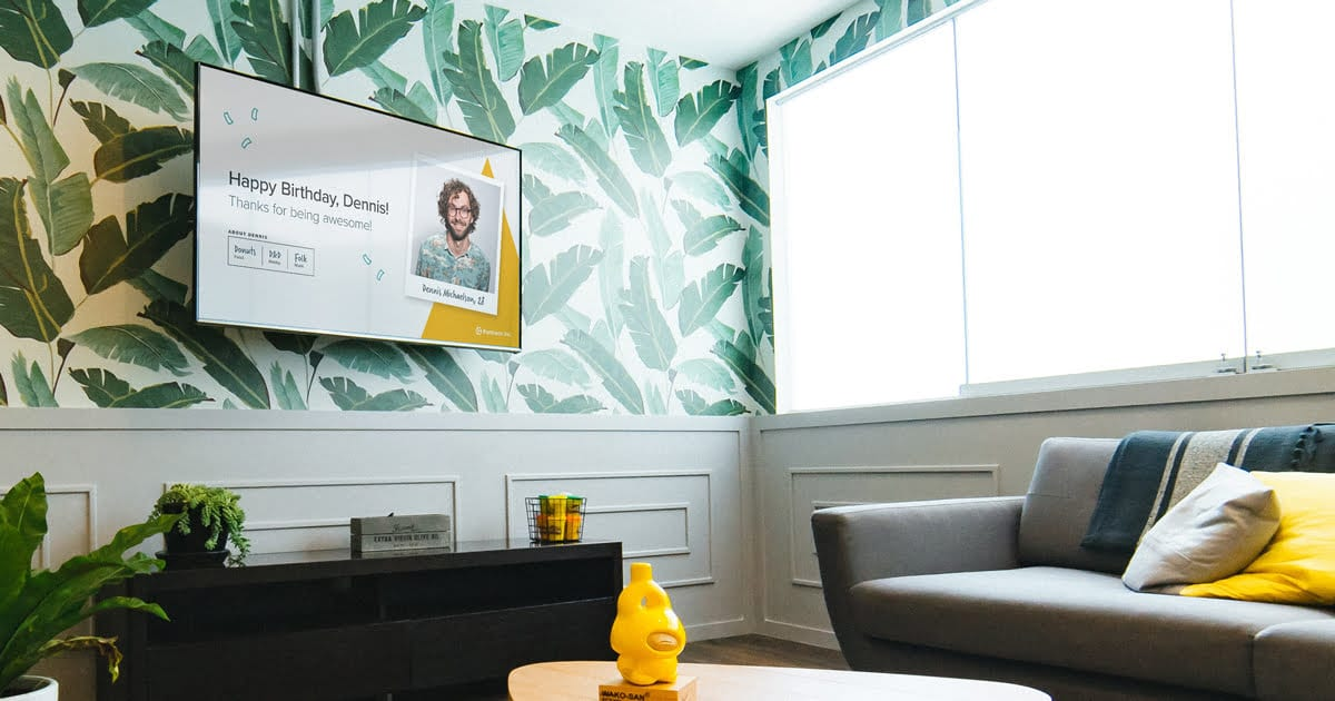 a bright, modern office space with green plant wallpaper and digital signage content on staff news
