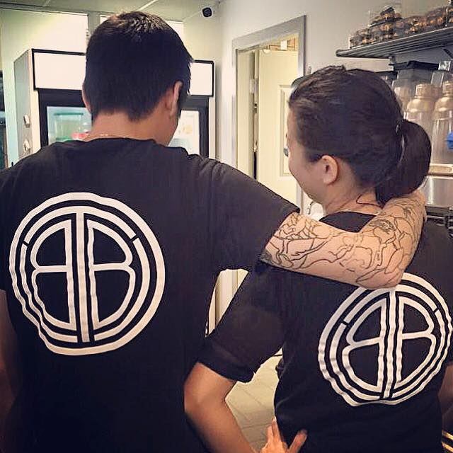 Karl Tang, Owner of The Bubble Tea Shop with his back turned so that the company logo on the back of his shirt is showing