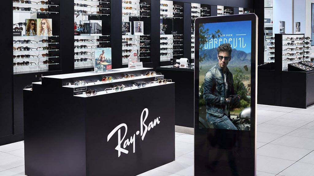 Digital signage kiosk display showing a branding design inside of a trendy eyewear store