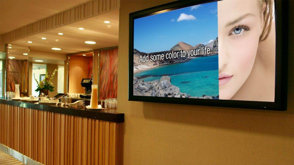Digital signage TV display beside the front desk of a hotel with a promotional design for the hotel spa